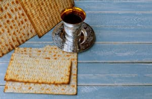 Jewish holiday, Holiday symbol passover matzo with kiddush cup of wine on wooden table