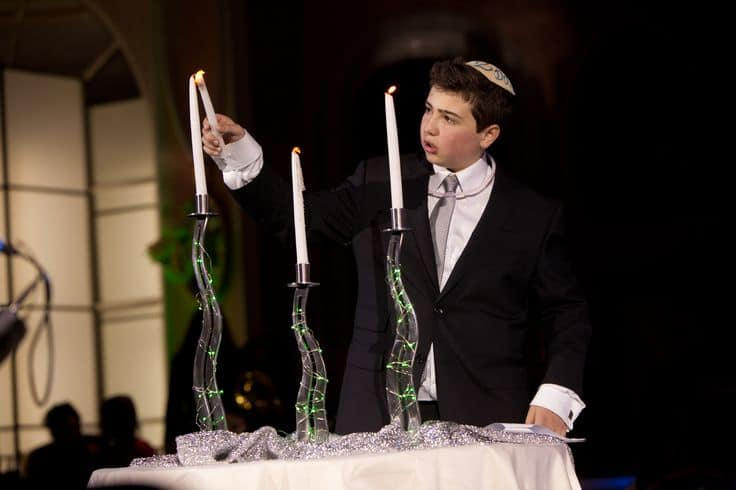 jewish boy lighting three candles at bar mitzvah lighting ceremony